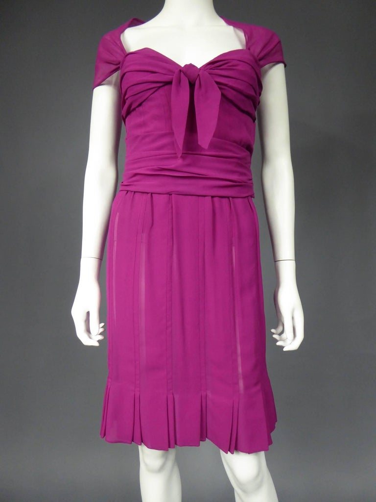 Circa 1989 - 1990  France  Cocktail dress in raspberry pink silk muslin . Bodice inspired by 1940's Fashion, fully corseted and lined with matching chiffon silk. Bodice sheathed to the hips, boned and reinforced on the chest. Chest preformed by a