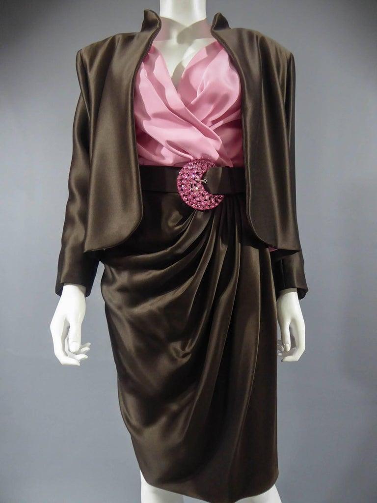 Circa 1989  France Haute Couture  Luxury evening set, Haute Couture skirt, blouse, jacket and   belt numbered 65123 from the Yves Saint Laurent 1989 Collection. The low-cut neckline blouse with wide shoulder pads in pink silk crepe is crossed at the