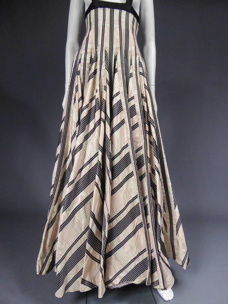 Circa 2000  France  Wide pleated sun skirt Rochas from the 2000s. Powdered pink silk taffetas with wide black and white stripes. Flat folds with folded seams widening from the hips in flare and giving a 360 ° amplitude. Suspenders and top of the