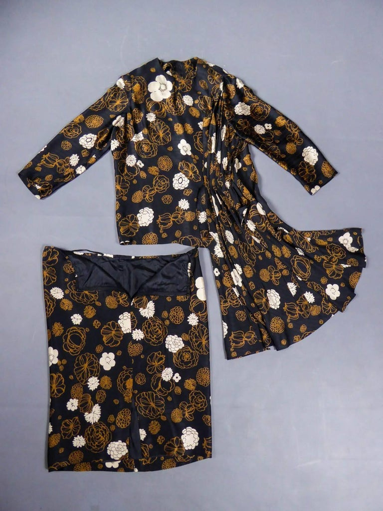 Circa 1980  France  Shirt skirt set Madame Grès Haute Couture from the 80s. Black silk satin with a matte and shiny effect, printed with light brown and white flowers. Asymmetrical pleated effect with small train on the hips. Blouse with long