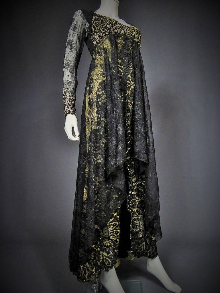 Circa 1988 - 1992  France  Evening dress Christian Lacroix Haute Couture from the beginning of the chic gothic movement dating back to the end of the 80s. Cream tulle background embroidered with gold lurex flowers and black calais lace on the dress.