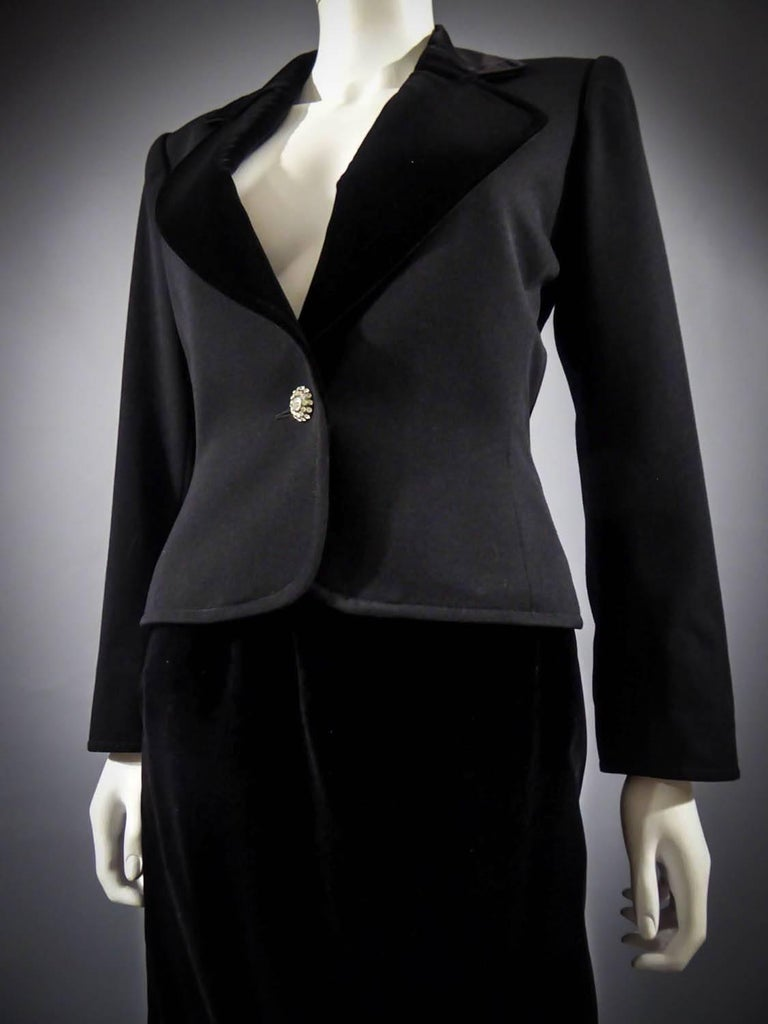 Circa 1980  France  Tuxedo suit skirt Yves Saint Laurent Rive Gauche with jewelry buttons. Skirt and lapel of jacket in black silk velvet. Straight skirt with pockets and side zip. Tuxedo jacket, flared on the hips, with small shoulder pads, in