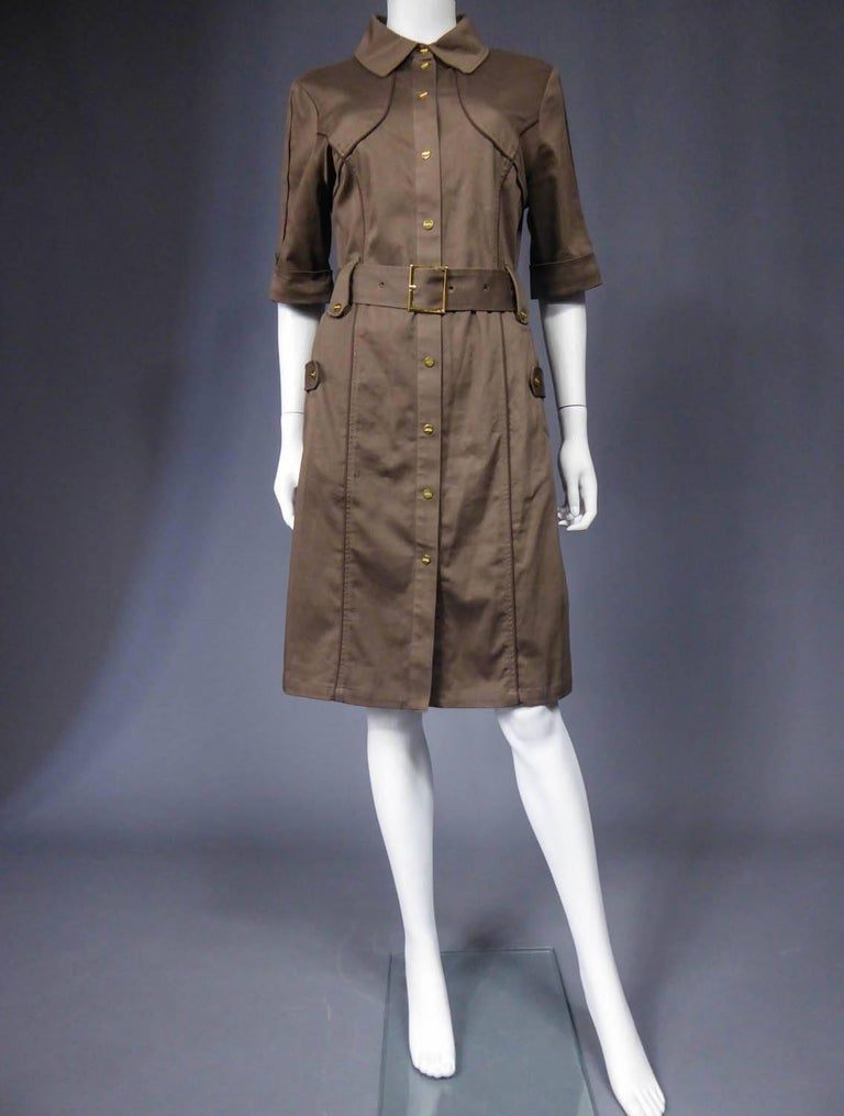 Circa 1970 - 1980  France  Sahararienne dress Rodier in chestnut cotton gabardine. Clear inspiration by Yves Saint Laurent. Dress entirely underlined with brown piping, flaps on pockets, belt and sleeves. Shirt-like collar from masculine