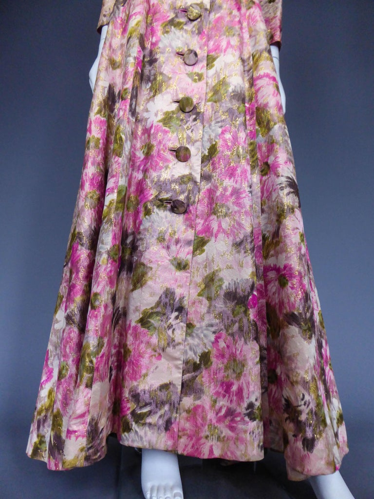 Circa 1935/1950 United States  Frock coak long dress in shaped gold-plated silk Elizabeth Arden's. Famous New York reference to 5th Avenue between the two World Wars and dressed as Hollywood stars. Decoration of large flowers printed on chain giving