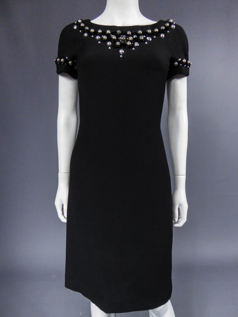 Circa 2005 France  Small black dress with boat neckline applied of jewelry of the Milanese designer Dolce Gabbana and dating from 2000/2010. Black jersey in stretch. Neckline and short sleeves adorned with cabochons and steel beads with fine black