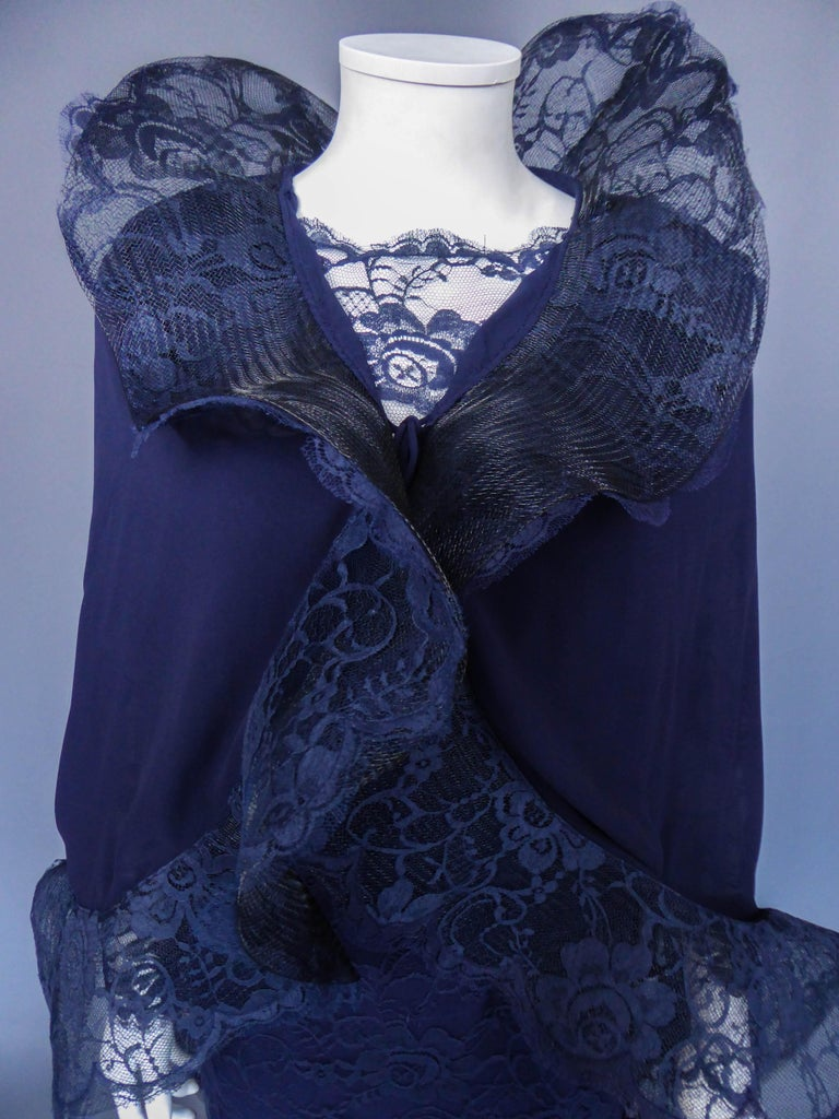 Circa 1985 France  Long evening dress and silk muslin and ruffle lace capeline by Pierre Cardin (attributed to) from the 1980s. Blue navy dress with a large transparent neckline and sleeves covered with matching Calais lace. Large rigid ruffles