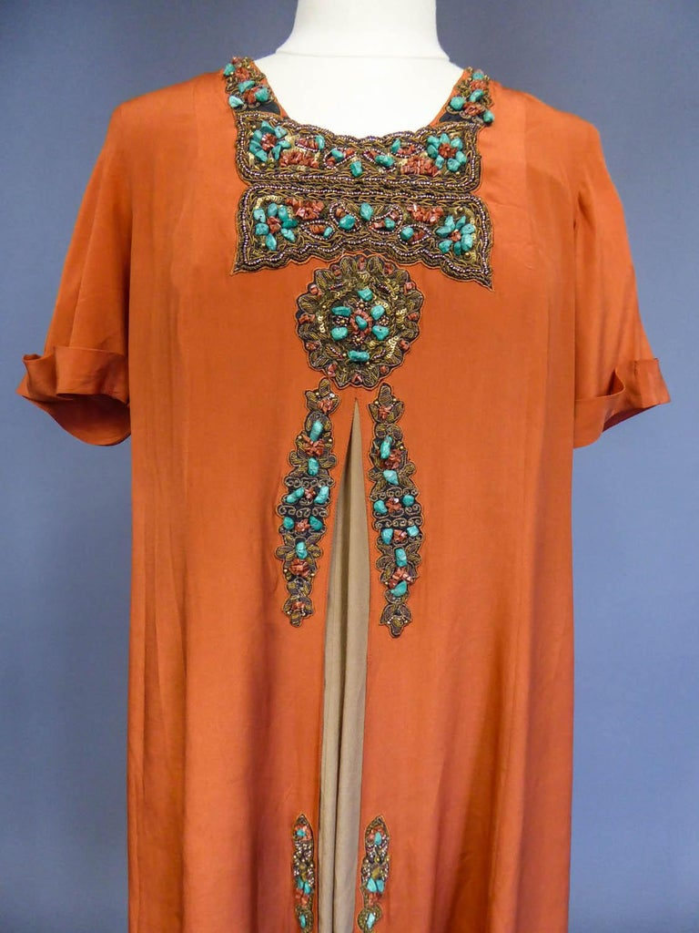 Circa 1915/1925 Europe  A surprising little jewel dress in the orientalist style of the 1920s. Orange rust silk crepe with rich embroidery of pearls, sequins and gold chenilles, all set with oranges raw stones and turquoises! Small short sleeves