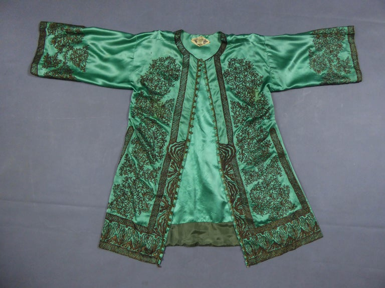 Circa 1910/1920 Asian production for France  Party or Evening kaftan kimono in green silk satin of the famous Parisian House Babani. Kimono cut slit on the sides. Closing on the front with faceted glass buttons. Rich chinese appliqué embroidery in