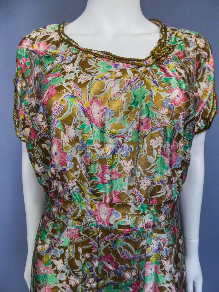 Circa 1940 Europe  Amazing little summer dress with flowers on a gold background dating very propably from the Second World War. Clever print on silk satin cream with surreal patterns popular in the 1940s thanks to Elsa Schiaparelli ... Fish, horse