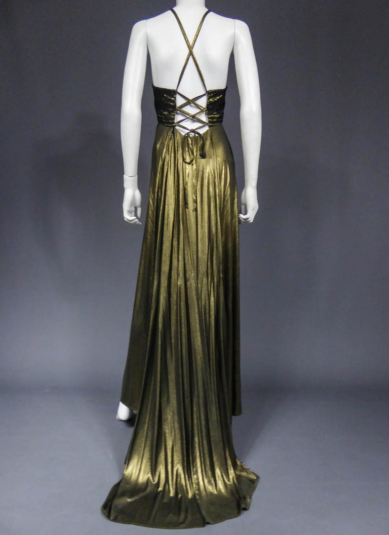 Circa 1995 France  Christian Lacroix haute couture evening gown in copper golden lamé from the 1990s. Savant lacing of back straps that cross at the back and at the chest. The latter is covered with black lace. Small train skirt of great elegance.