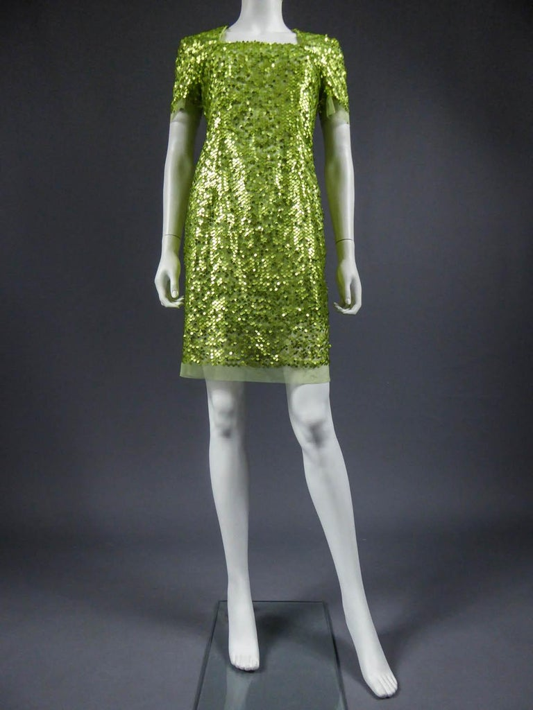 Circa 1990 France  Short dress in green tulle embroidered with iridescent green glitter. Square collar and slin-tight, it closes at the back with a zip. Lining in green synthetic. No label but Couture hand made work. Very good condition of color and