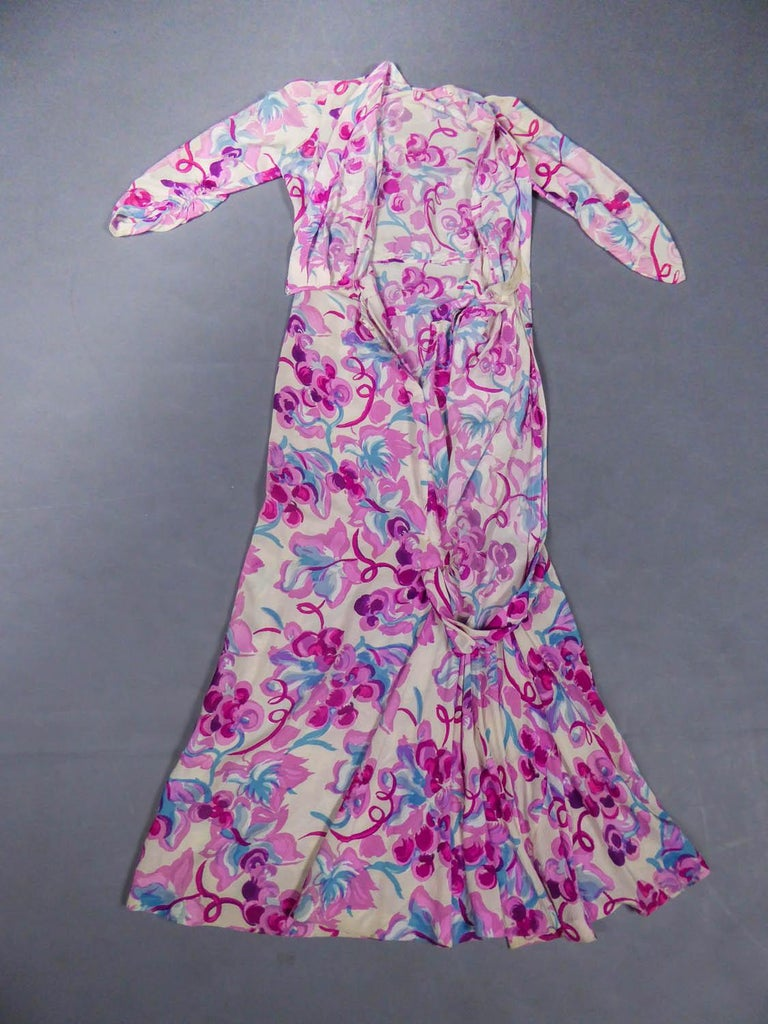 Circa 1940 France  Summer dress in cream silk crepe with patterns of grapes in pink, fuchsia, aubergine and sky blue. Sleeves three-quarter, closes on the front by a drape effect. Slightly damaged on the closure of the dress, otherwise very good
