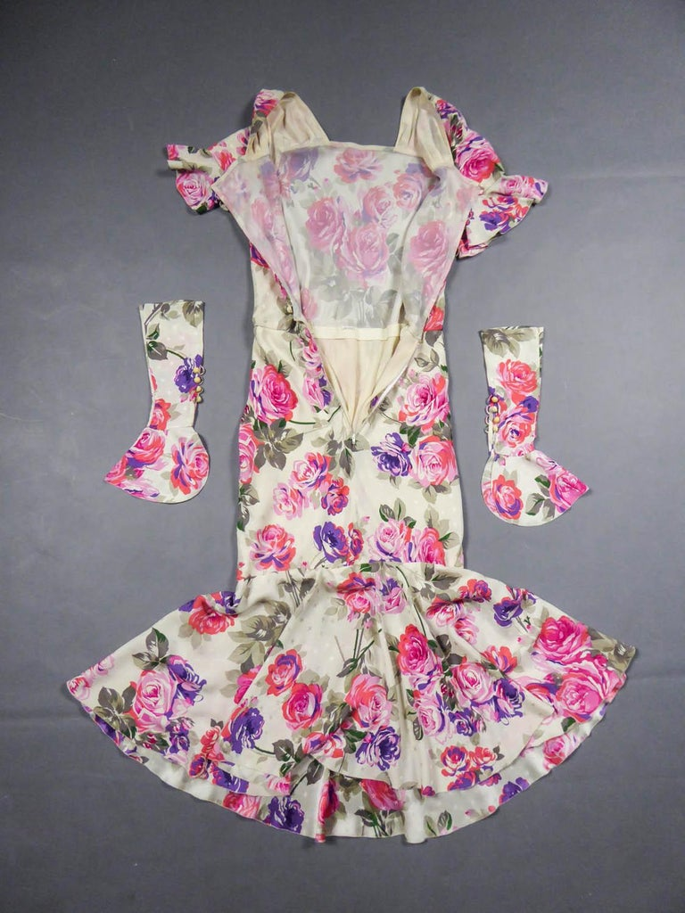 Circa 1985 France  Jeanne Lanvin summer dress in cream satin prints with patterns of roses in shades of pink, purple, coral and khaki. Straight collar, ruffle sleeve and removable cuffs covering the hand and simulating fingerless glove, closing with