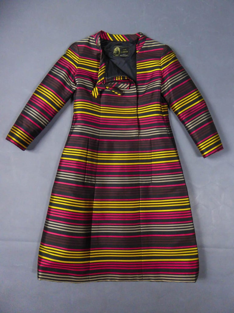 Circa 1965 France  Elegantcocktail dress in black gazar and thin stripes gold, vermilion, gray and garnet-colored from the famous Maison Lanvin directed by Jules François Grahay since 1963. Long sleeves and mandarin collar finished with a rigid