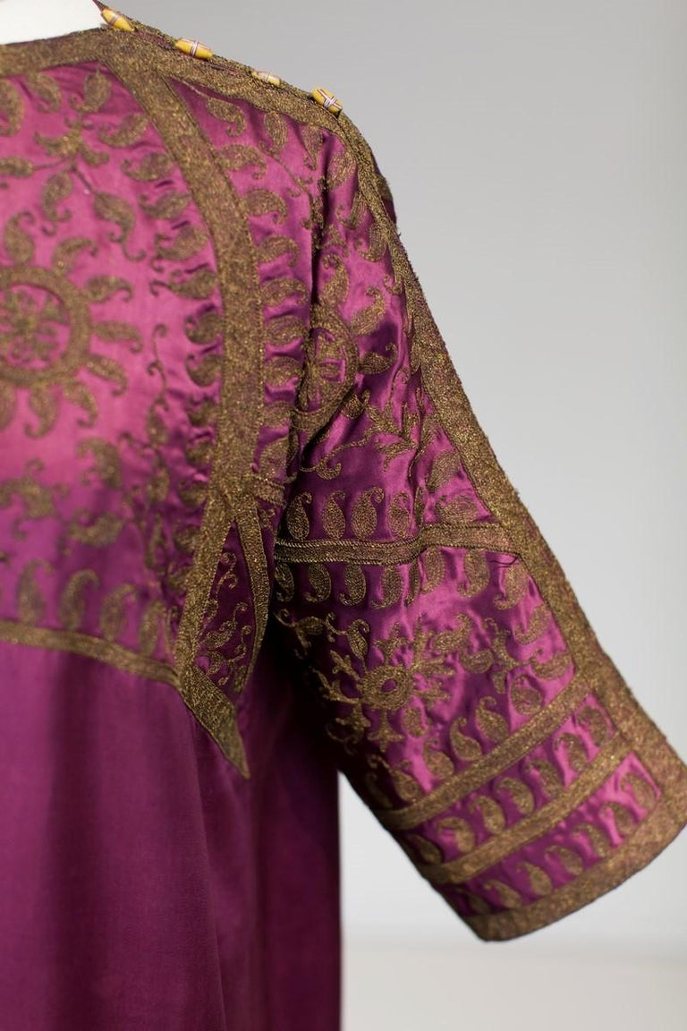 Circa 1915/1920 France  Kaftan interior or evening dress in the Orientalist and Indian taste developed by Madame Babani, famous Parisian seamstress who dressed the society and artistic elite after the First World War. Large aubergine silk satin long