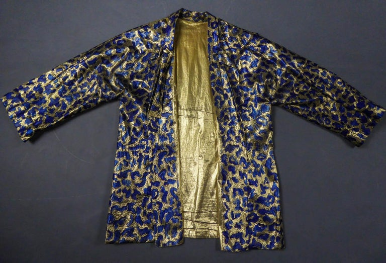 Circa 1960 France  Gold lamé jacket handpainted in blue and black outlines of abstract patterns in the way of the French Impressionist painter Henri Matisse. Kimono cut, long sleeves and high collar adorned with 2 sides in the same fabric to tie on