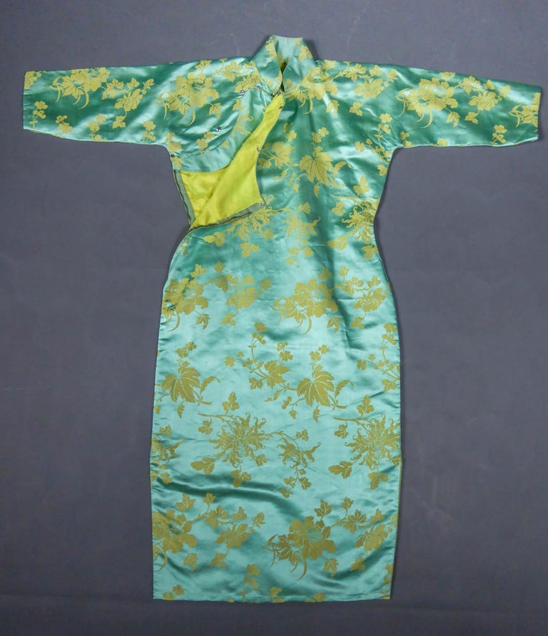 Circa 1950/1960 France  Skin-tight chinese dress called qipao or cheongsam in sky-blue and straw-yellow silk damask dating from the years 1950/1960. Damask sky-blue satin background with large stylized flowers, peonies and / or chrysanthemums (?) in