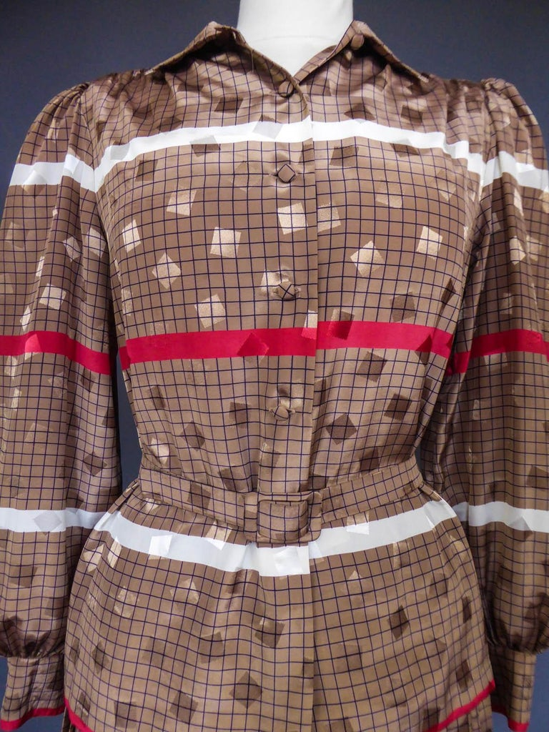 Circa 1980 France  Pleated skirt and blouse in brown polyester with black plaid, pink and white stripes and iridescent brown cubes dating from the 1980s. Without label but Cacharel very probably type. Blouse with puff sleeves tightened at the waist