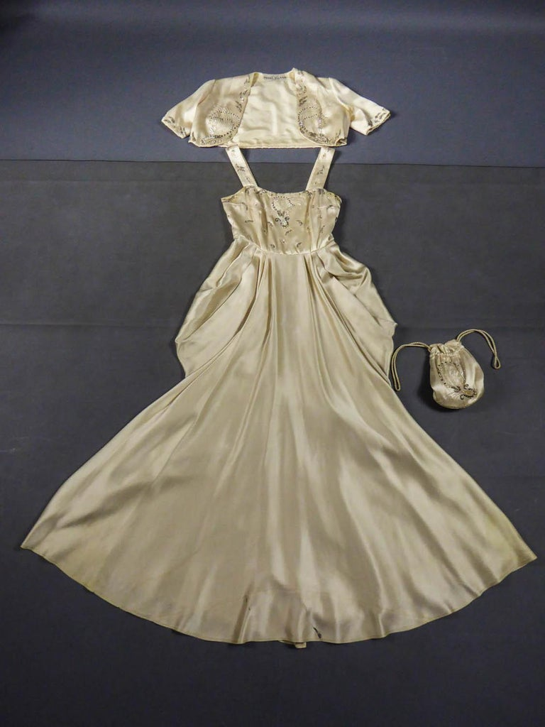 Circa 1950 France  Pierre Balmain Paris evening or ceremony dress with matching bolero and purse from the 1950s. Ivory Duchess satin embroidered with white and silver tulbular pearls, cultured pearls, silver sequins and iridescent sequins. Bolero