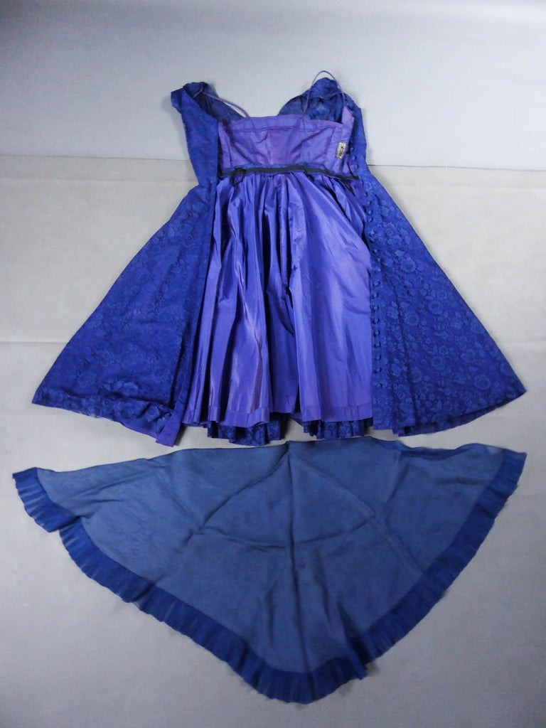 Circa 1950 France  A Louis Féraud Haute Couture dress in Calais lace with large bouquets of navy blue flowers dating from the early 50s. Dress with flared corolle skirt from the waist with a navy bluetulle underskirt and a purple taffeta slip