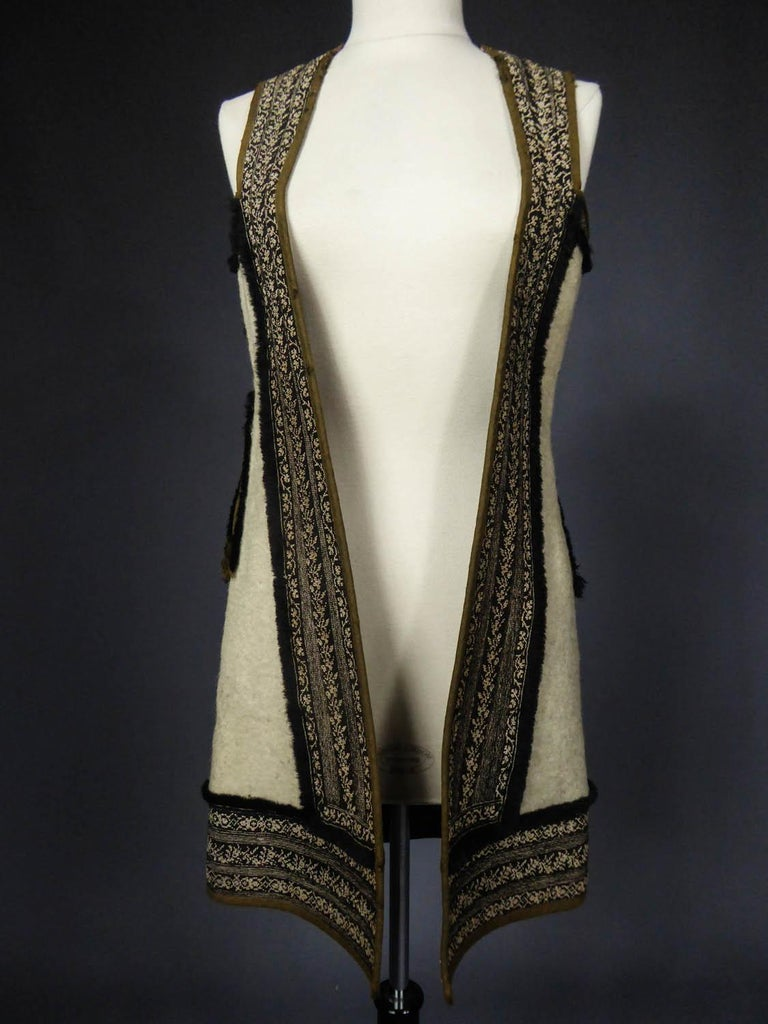 Circa 1900 Greece - Macedonia - Albania (?)  Long vest or sleeveless coat in thick wool finely embroidered at the petit point dating from the early twentieth century and originating in Macedonia or Albania. Thick fluffy ivory wool sewn of black