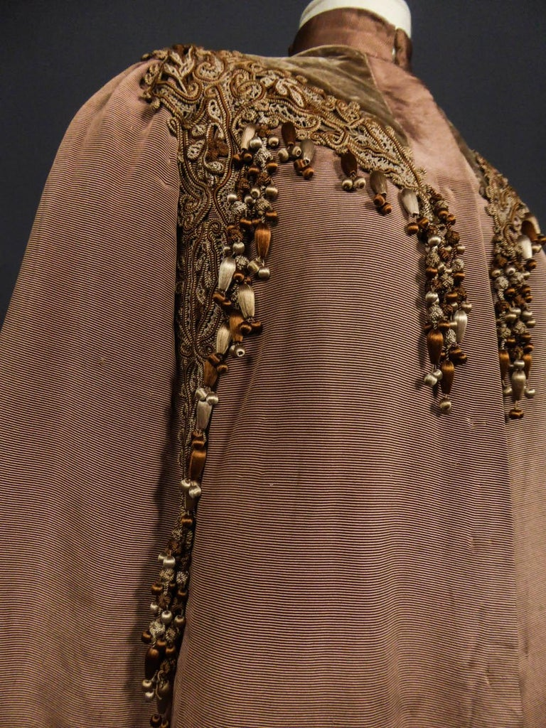 Circa 1890 - 1905 France  Large evening Cape in chestnut silk ottoman embroidered with trimmings dating from the late nineteenth century in the style of the french designer Emile Pingat. Cut to the shape of the shoulders, small raised collar, this