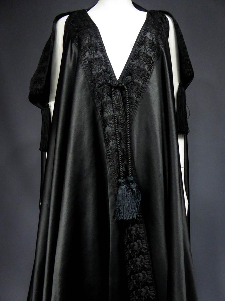 Circa 1920 England  Amazing evening cape in the Djellaba spirit in black Duchesse satin silk by Liberty and Codating from the years 1920 - 1930. Cape with small slashed sleeves and pompoms of silk trimmings to pass the arms. Beautiful black duchess