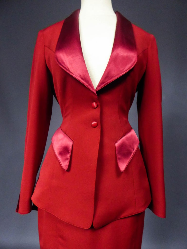 Circa 1990 France  Thierry Mugler jacket and skirt set in red brushed wool. Fitted jacket with large cleavage. Lapel collar, pockets and closure of the sleeves covered with red silk satin. Jacket in peak, low-neckedon the back and adorned with a