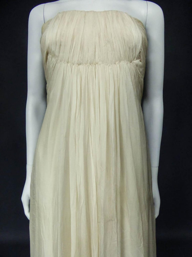 Circa 1970 France  Anonymous haute couture evening dress in chiffon and cream silk crepe from the 1970s. Probably fromJean Dessès or Carven designer house(?). An empire-inspired, high-waisted bustierdress with work of pleats at the chest.