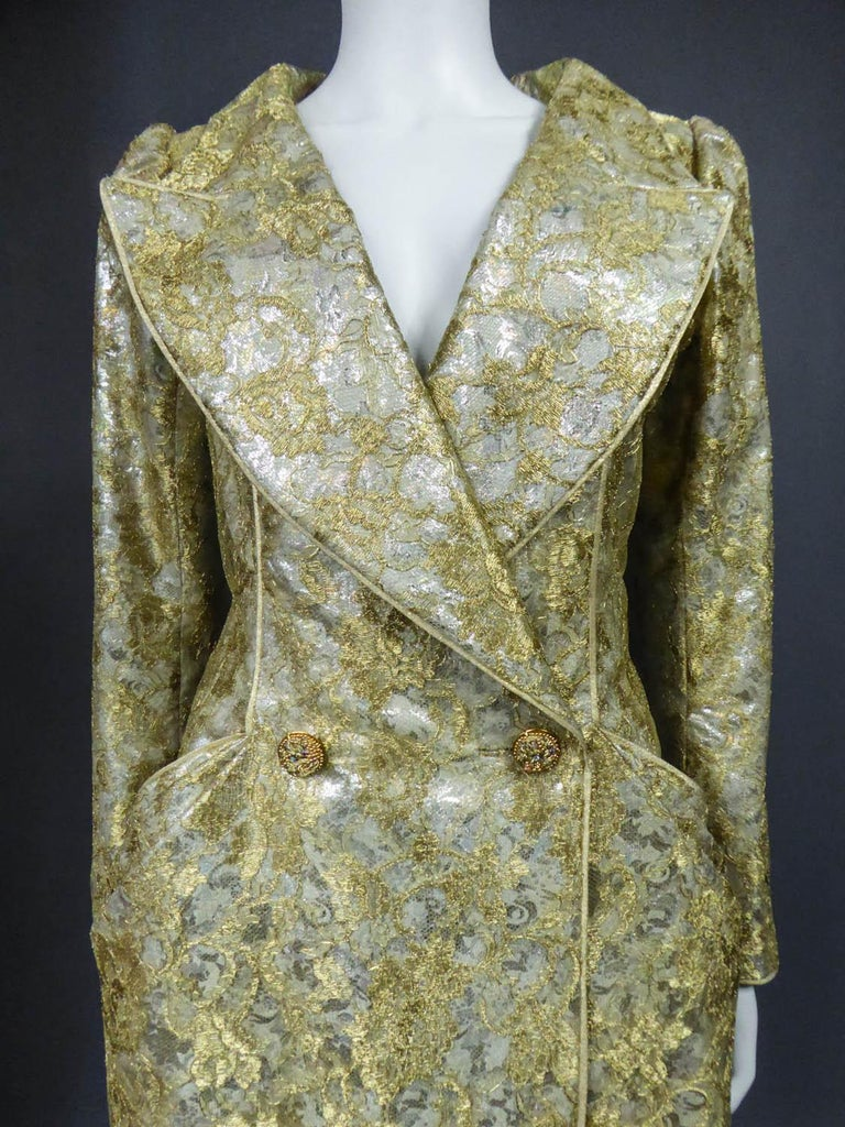 Circa 1990 France  Haute Couture evening coat dress by Emanuel Ungaro from the 1990s. Silver lamé with floral patterns covered with gold lace overlay. Wide collar with plunging cleavage on the chest, hips marked by two side pockets with three