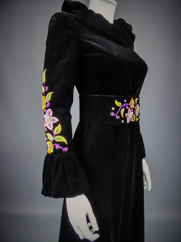 Circa 1990 France  Long evening dress in black silk velvet by Jean-Louis Scherrer Haute Couture dating from the 1990s. Pleated collar in bouillonné velvet ruff found on the sleeves and the bottom of the dress which is flared. Psyquedelic embroidery