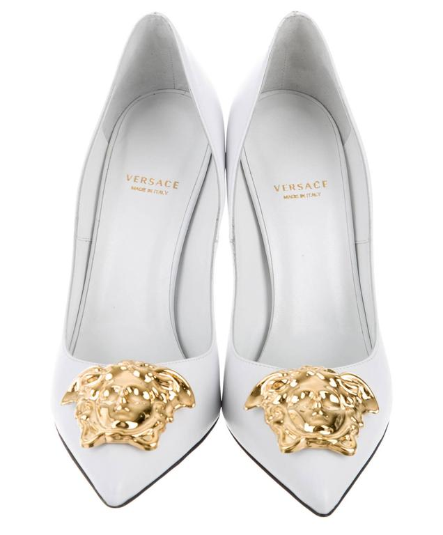 White leather Medusa pumps from Versace featuring a pointed toe, a branded insole and a gold-tone high stiletto heel. Gold-tone Medusa embellishment at tops. Italian Size - 38.5 Heel - 4.5 inches (11.5 cm). Lining Composition:  Leather 100% Outer
