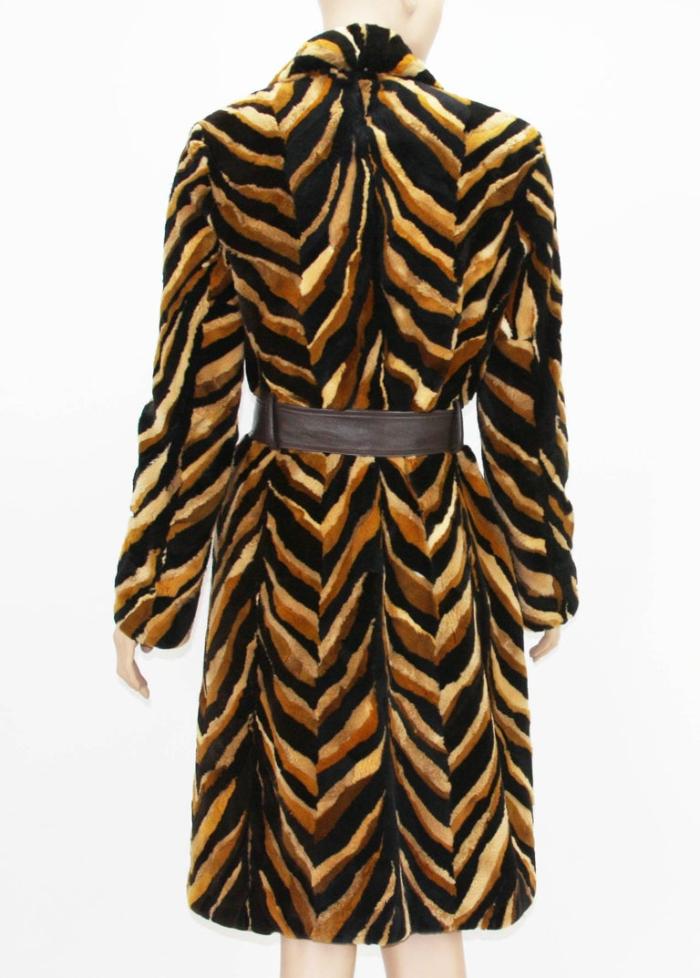 Intricately detailed coat constructed with different shades of mink (black, browns, tan) forming a large chevron pattern. Vintage Gianni Versace Couture Sheared Mink Belted Coat. Italian size - 42. 89% Mink, 11% Leather. Fully Lined in brown lining