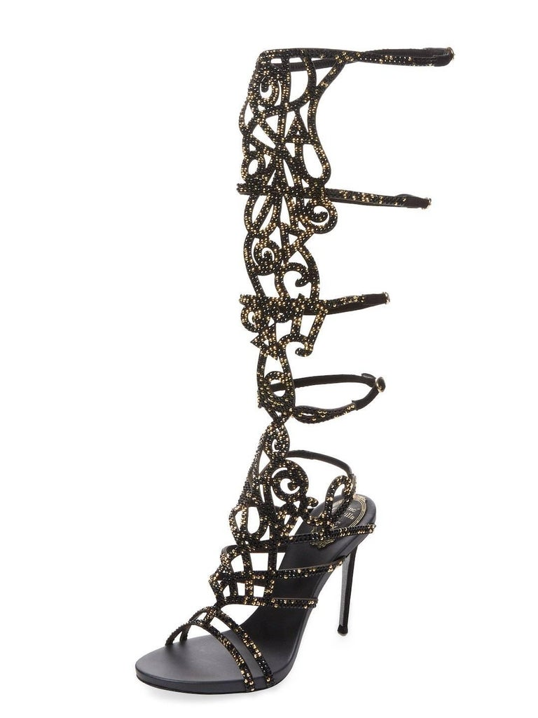Rene Caovilla Knee-High Gladiator Sandals. Designer size 36 - US 6 Leather upper with Swarovski crystals - black and gold. 4 inches heel, Leather Lining, Gold Tone Buckles. 15 inches H shaft with Buckled Straps. Signature Glittered Sole. Made in