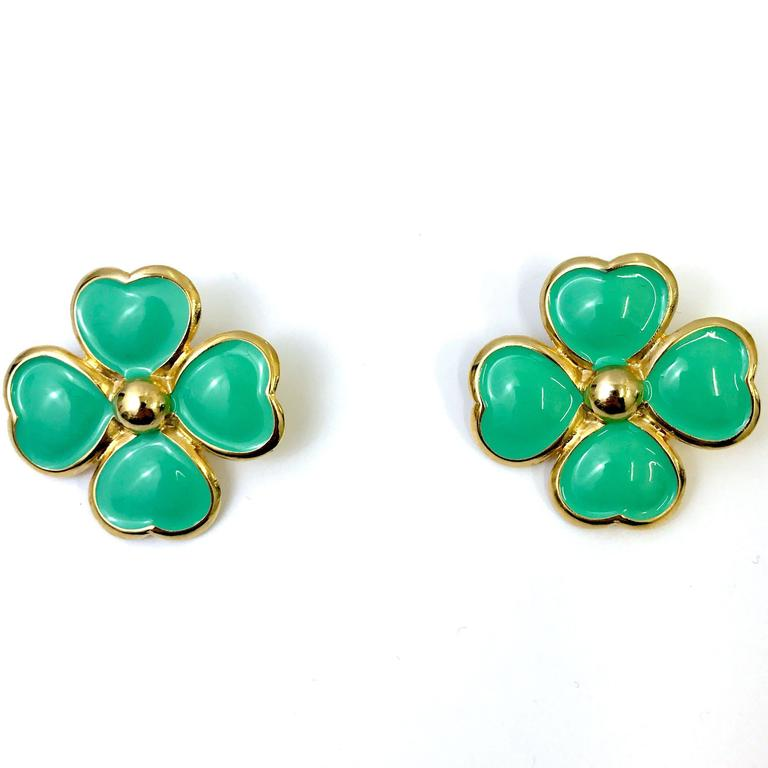 These flower clip on earrings by Gianni Versace feature a gold tone metal base. The real highlight of the piece is the light green enamel colouring which lifts any outfit. Finished with Gianni Versace made in italy stamp.