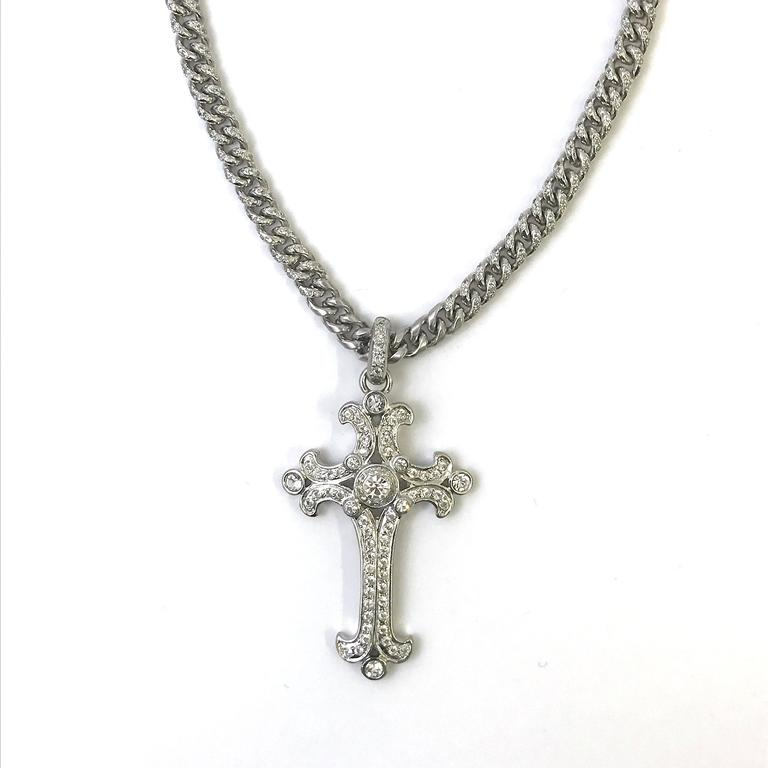 This 1990's Gianni Versace cross pendent necklace is masterpiece whilst offering a timeless classic style. The silver tone metal curb chain has a beautiful stone detail towards the pendant and the rest of the chain has a subtle brushed and polished