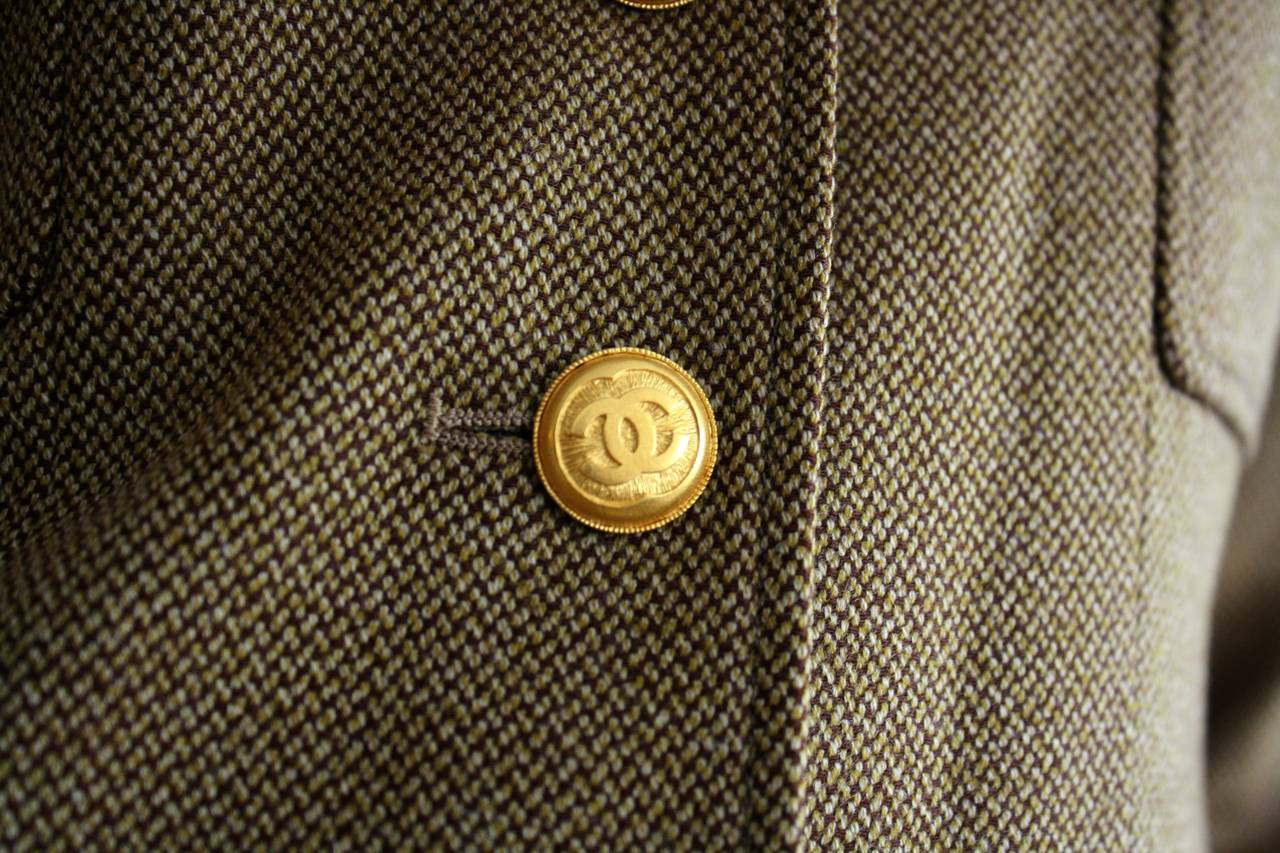 Amazing Vintage Chanel Blazer. This beauty is from the Autumn 1996 Runway Collection. Wonderful tan, olive and brown colors. Intricate detail at seams. Military style. Signature CC logo buttons at cuffs, and down bodice. Interior chain at waist to