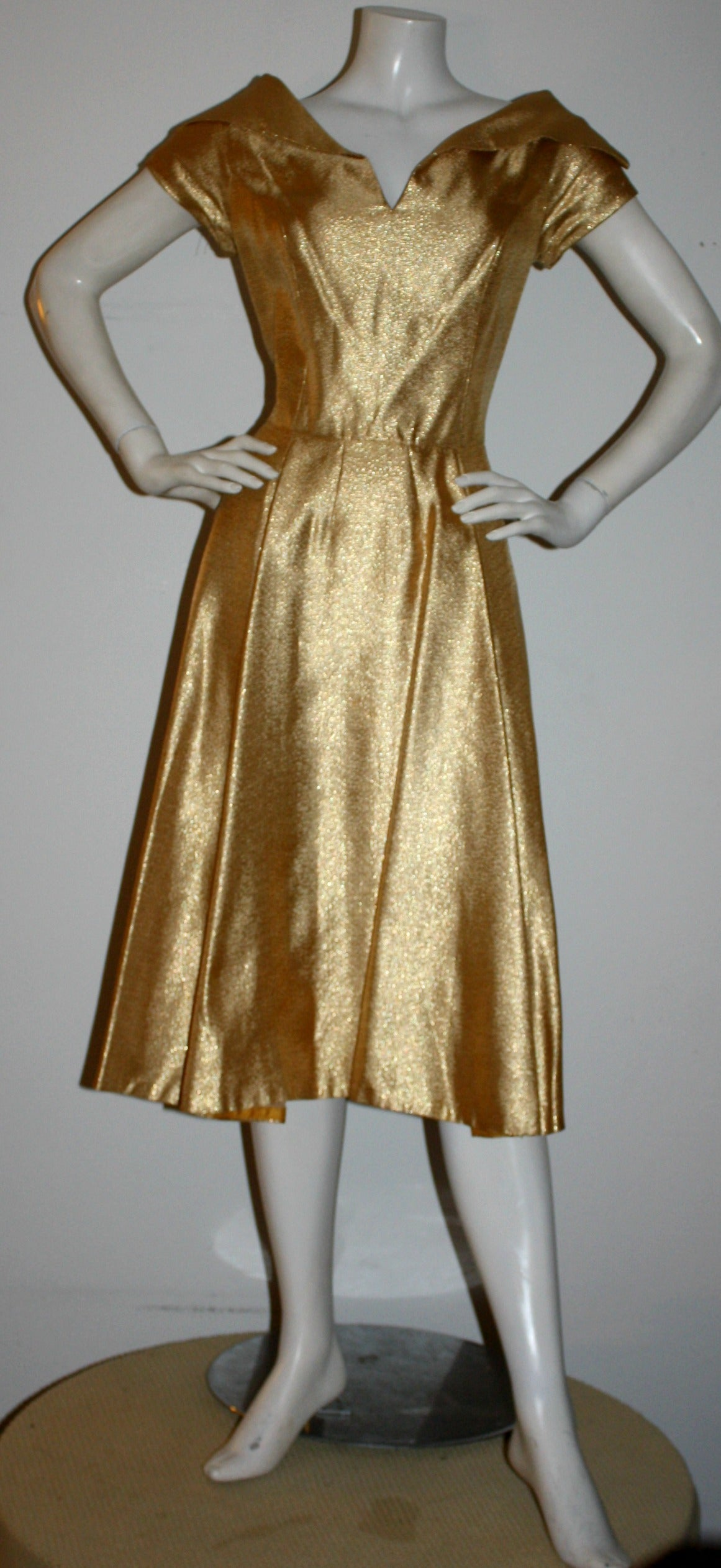 Gorgeous 1950s gold metallic dress! This beauty features a dramatic collar, with a note-worthy full skirt (perfect to add a crinoline)! Looks fantastic for any cocktail party, and is great on the dance floor! Fully lined in yellow silk, with metal