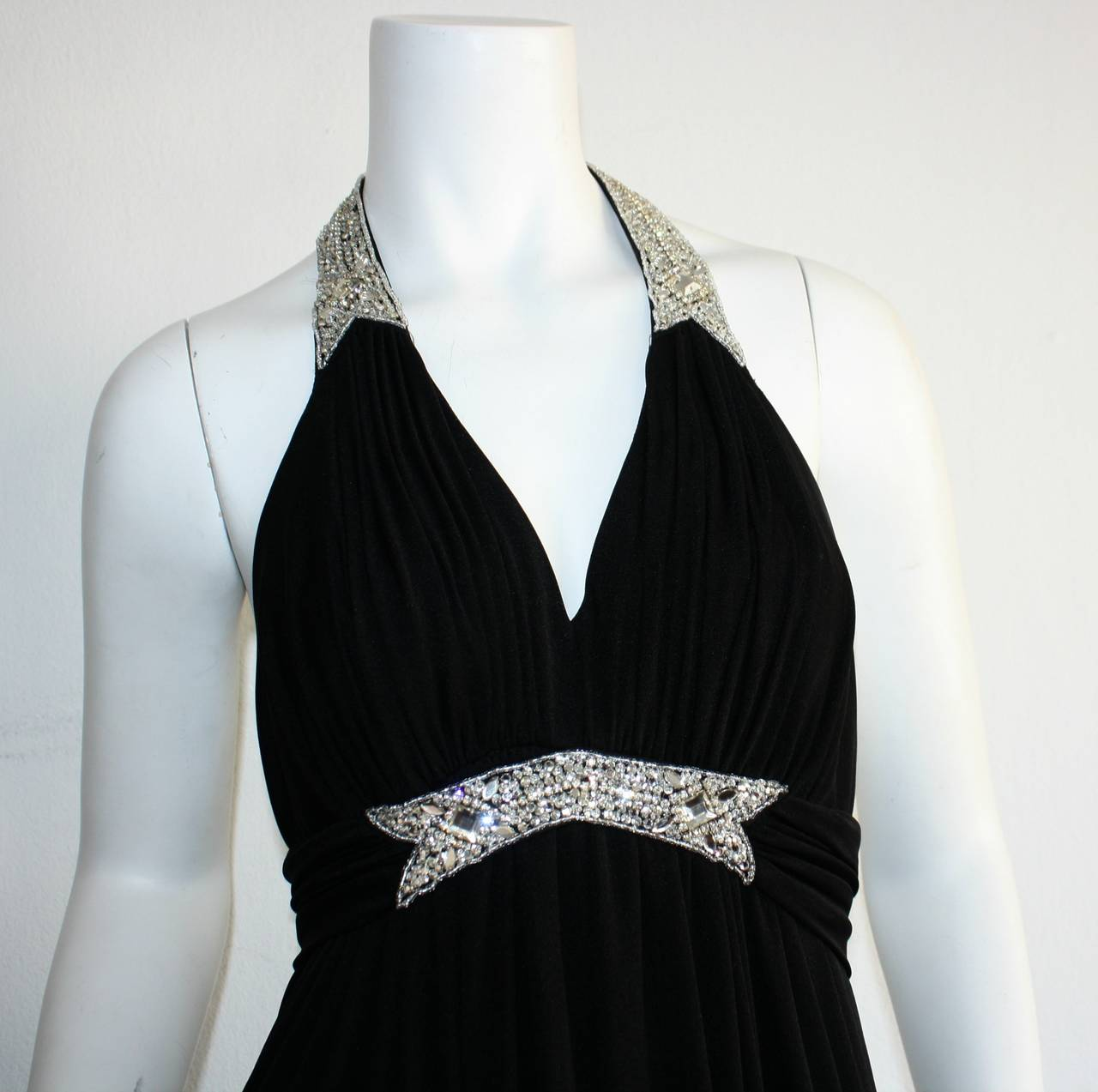 Simply divine vintage Victoria Royal black jersey halter dress! Perfect Grecian style, with rhinestones encrusted at waist, and on halter. Beautiful pleating that screams elegance! Rhinestones are clear, and sparkly. Hidden zipper up back, with