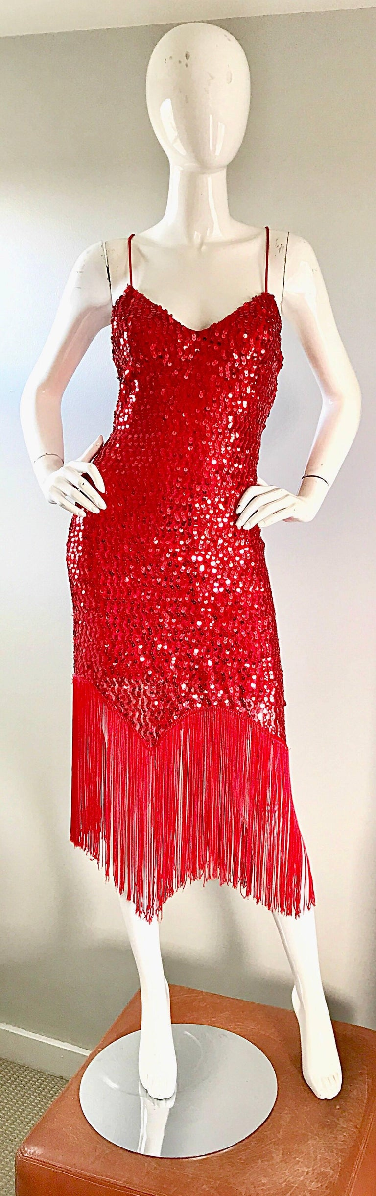 Fabulous 70s does 20s lipstick red fully sequined fringe hem sleeveless flapper dress! Features thousands of hand-sewn red sequins throughout. Asymmetrical handkerchief fringed hem. Fully lined. Hidden zipper up the side. Looks great alone or
