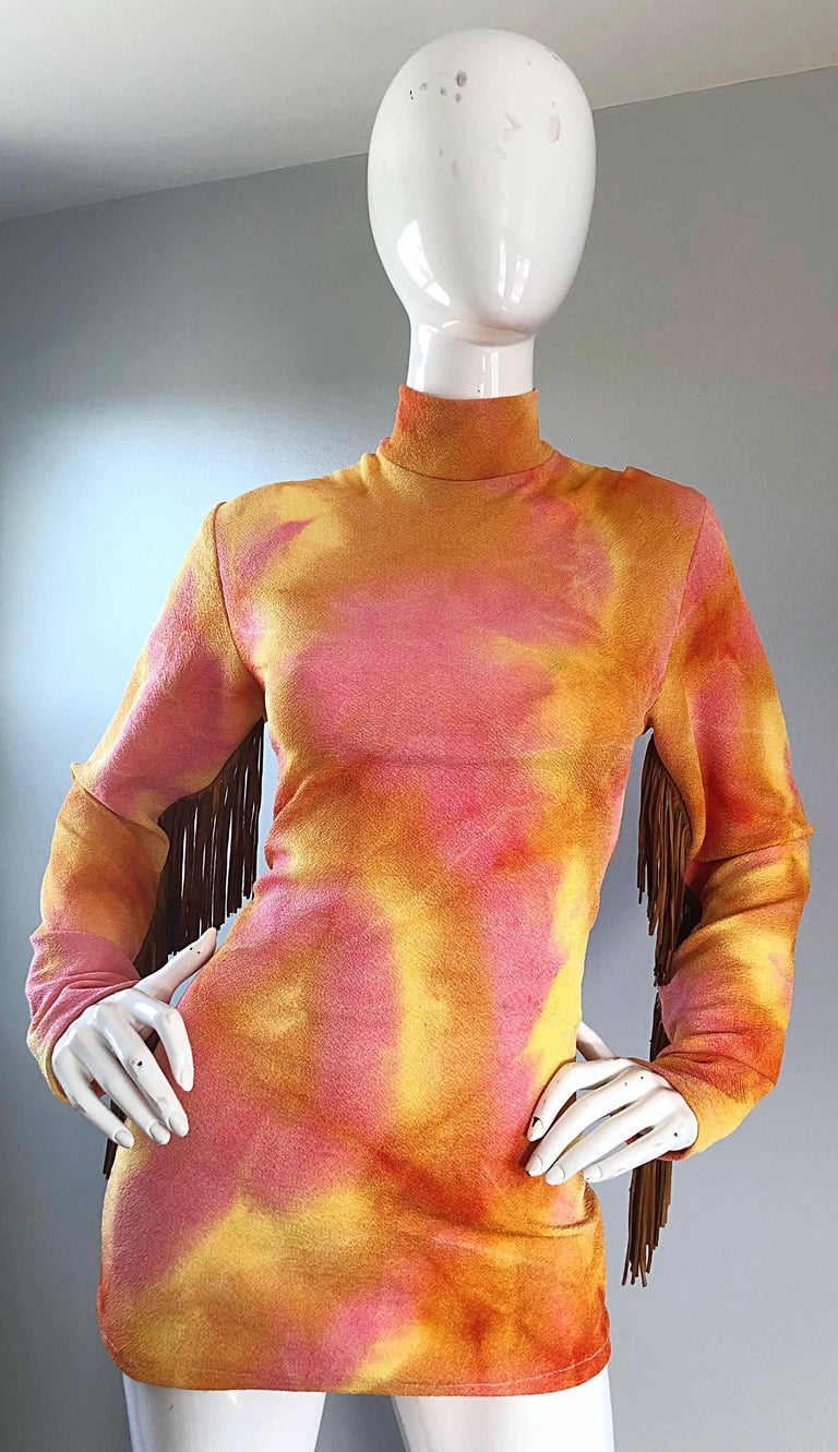 Amazing vintage 70s pink and orange tie dye tunic top! Features a flattering stretch to fit silhouette, with a high mock neck. Brown / tan leather suede fringe on the back of each sleeve. Great belted or alone, and can easily be dressed up or down.