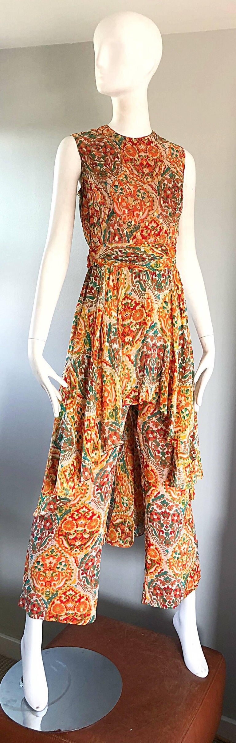 Amazing 70s OSCAR DE LA RENTA silk wide leg boho batik print jumpsuit, with attached skirt! Features vibrant colors of orange, green, brown, burgundy, yellow throughout. Fitted bodice features gold silk threading throughout. Wide palazzo legs. Full