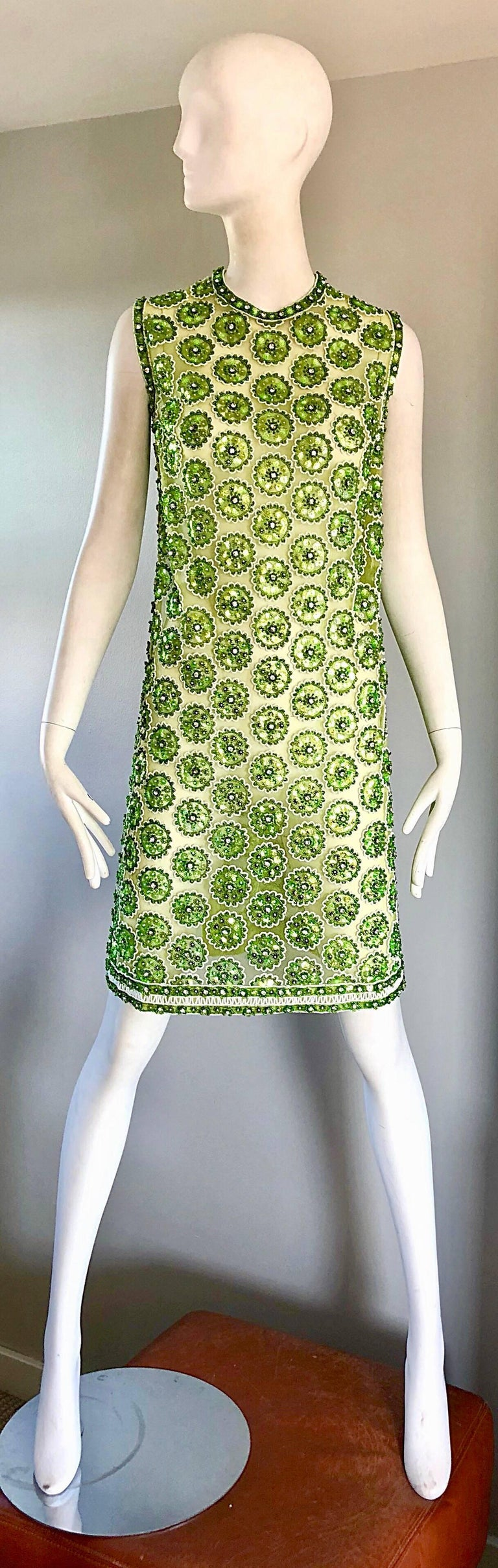 Chic 1960s fully sequined and beaded mesh demi couture tunic dress! Features thousands of hand-sewn sequins, rhinestones, and beads throughout to form flower shapes. Full metal zipper up the back with hook-and-eye closure. Semi sheer net mesh. High