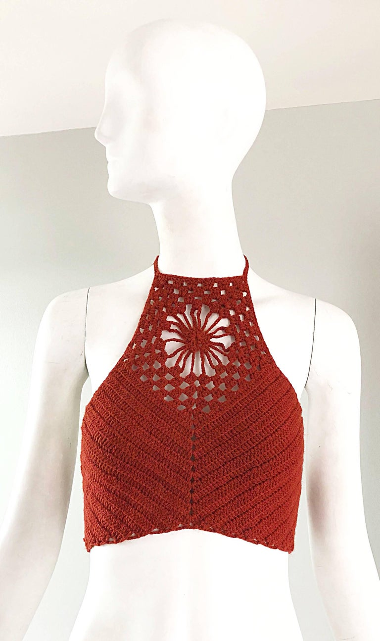Sexy 1970s hand crochet woven burnt orange halter crop top! Features a woven flower above the center bust. Ties at the back, and at back neck. Great with shorts, jeans or a skirt. In great unworn condition.  Approximately Size Extra Small - Medium