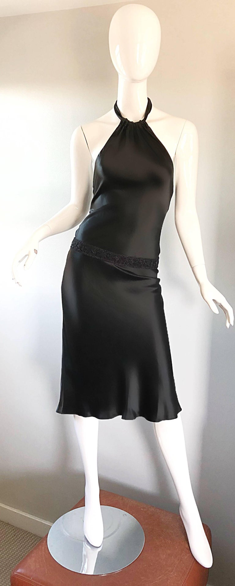 Striking 1990s VERA WANG black slinky beaded halter dress! Features a lovely silhouette that flatters an array of body shapes. Slightly dropped beaded waist gives an ode to the 20s. Hidden zipper up the side with hook-and-eye closure. Halter ties at