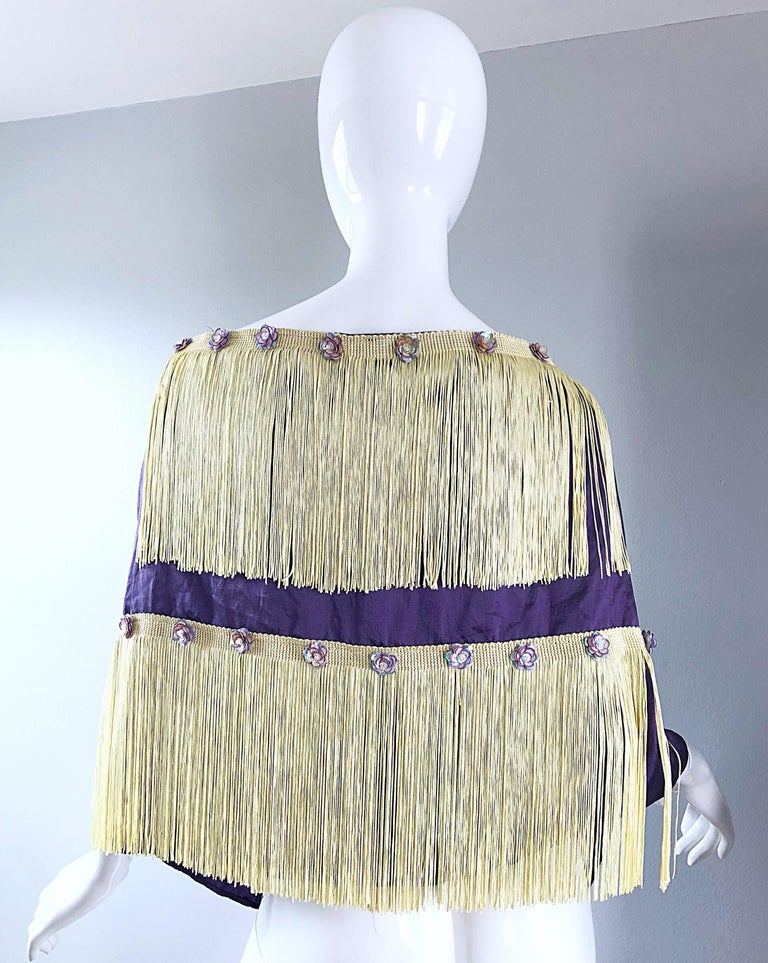 Beautiful 1950s purple and ivory fringed sequined large shawl / stole! Features a soft purple / lavender color with two layers of ivory fringe. Iridescent purple sequins in the shape of flowers hand-sewn throughout. The perfect accessory that can