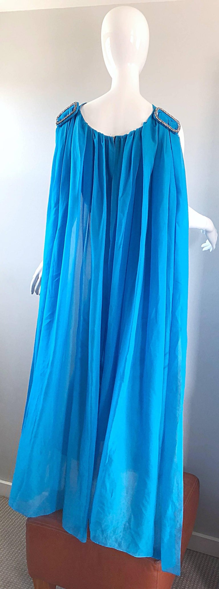 Incredible late 60s turquoise blue chiffon rhinestone encrusted gown with attached cape! Wonderful tailored fit with a fitted bodice and skirt. Attached semi sheer chiffon cape features a large rhinestone encrusted buckle on each back shoulder.