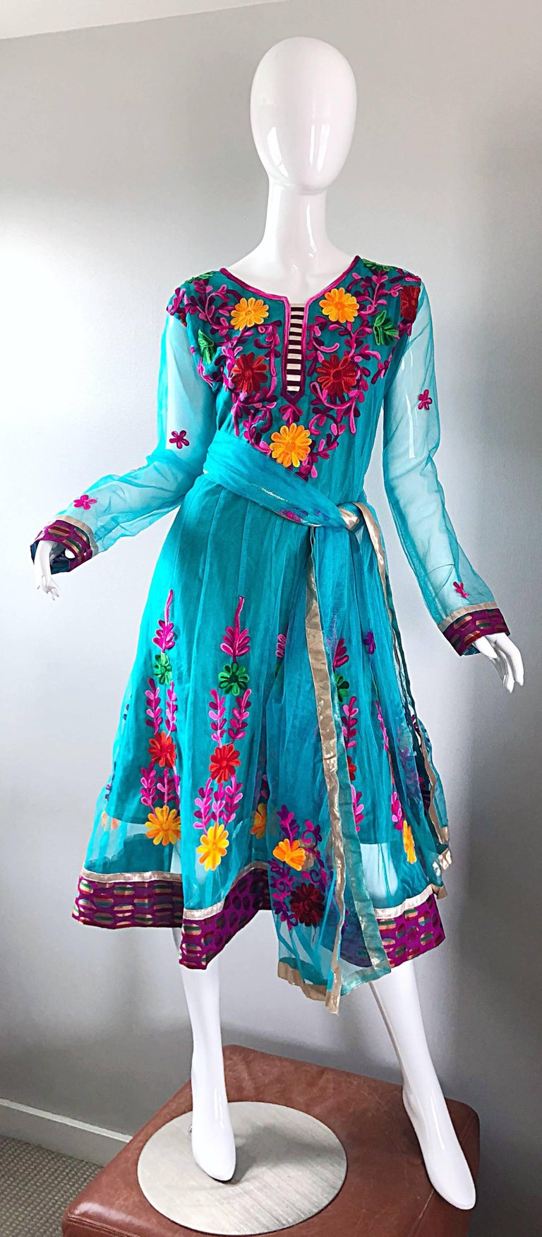 Gorgeous 1970s turquoise blue colorful embrodiered Indian boho kurta dress and sash belt! Features vibrant colored hand embrodiered flowers in fuchsia, purple, red, marigold yellow, pink, and green throughout. Gauze overlay with semi-sheer long
