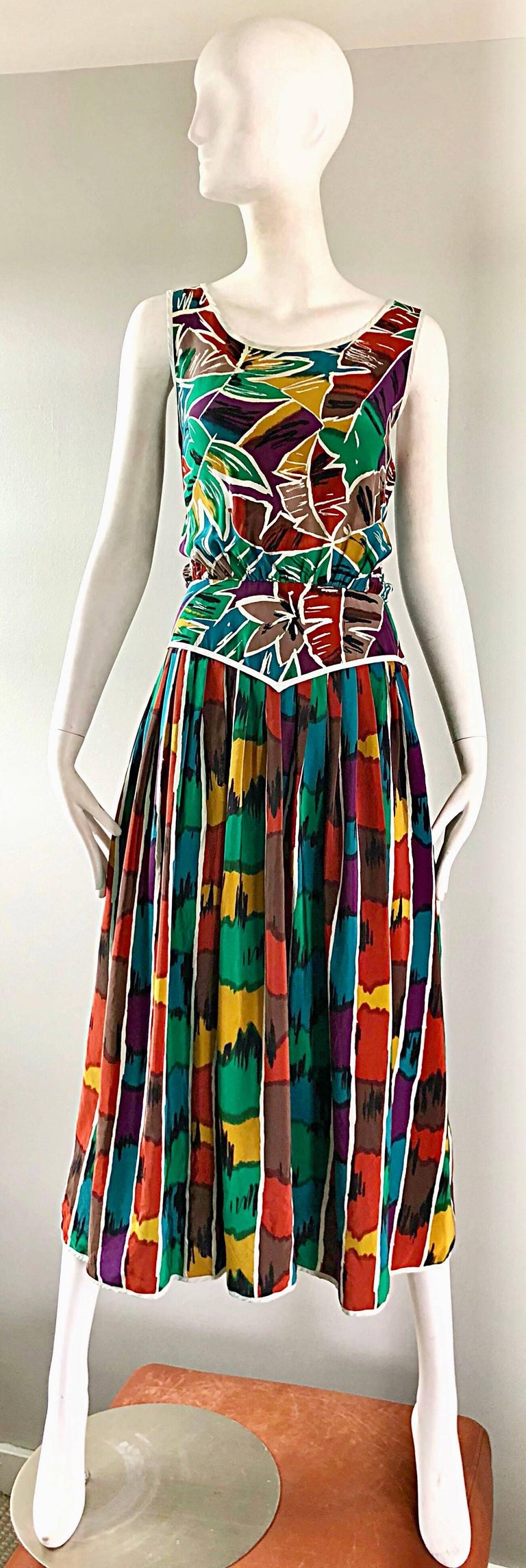 Chic vintage Oscar de la Renta kaleidoscope / Ikat tropical print silk midi dress! Features a flattering tailored bodice, with a loose fitting forgiving full skirt. Vibrant colors of rust, kelly green, burnt orange, teal blue, purple, white and