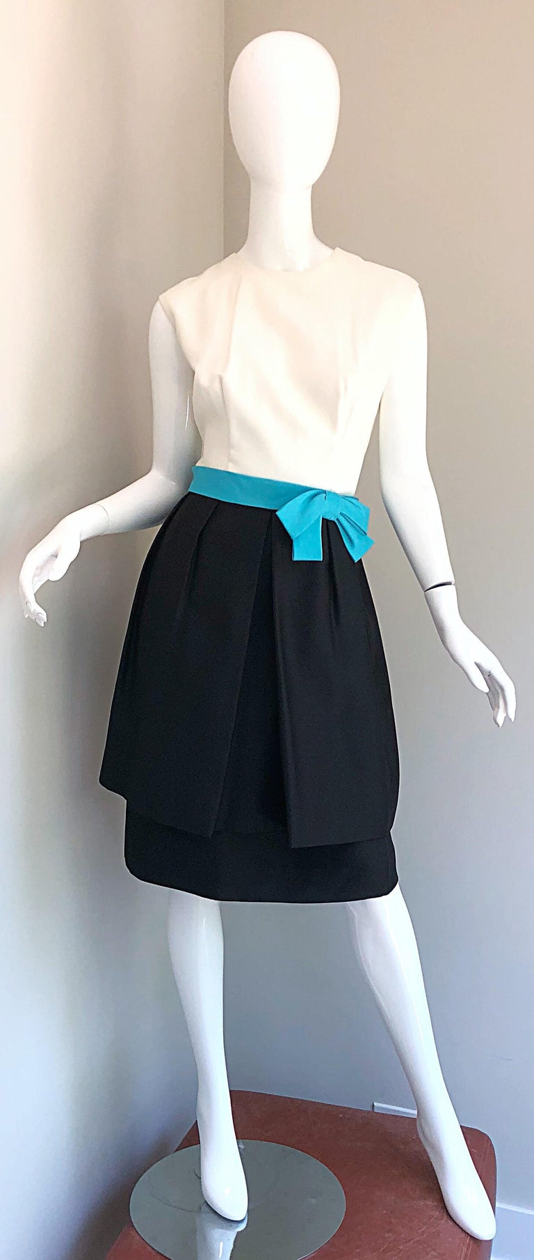 Beautiful late 1950s B. ALTMAN black and white and turquoise blue silk cocktail dress! Features a fitted white bodice with a black full skirt and nipped hem. Attached turquoise blue bow belt adds a pop of color. Full metal zipper up the back with